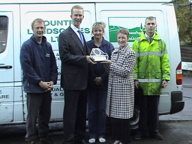 Yvonne Lyon of ChamberLink presenting the Investor in People Plaque to Lee Thorne MD with (from the right) James Taylor - Apprentice Landscaper Gardener Anita Martin - Operations Supervisor, and Craig Goldsworthy - Foreman